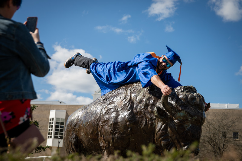 Students come to North Campus on May 16, 2020 to take photos in celebration of their graduations from various programs. The ceremonies were all held virtually because of the COVID-19 response. David Hooper, who earned a BS in engineering, poses for photos with the Bronze Buffalo, as his wife Maggie is the photographer.<br /> <br /> Photographer: Meredith Forrest Kulwicki