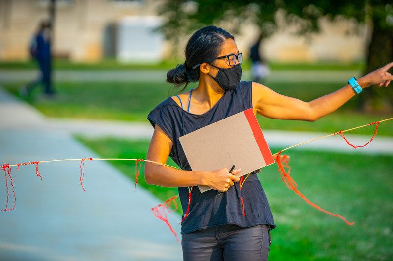 Students in a Media Architecture test run their physical distancing devices as part of a class with Joyce Hwang, with Architecture and Planning, in September 2020 on the Crosby Lawn on South Campus.<br /> <br /> Photographer: Douglas Levere<br /> <br /> This image has been approved by UB's Office of Environment, Health and Safety to align with current (fall 2020) health and safety regulations during the COVID-19 pandemic.