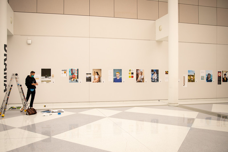 Jacob Vogan, curator of Show Your Work, installs more portraits for the show in the atrium of the Center for the Arts in September 2020. The show is presented by the UB Arts Collaboratory and will be on display through the spring of 2021.<br /> <br /> Photographer: Meredith Forrest Kulwicki<br /> <br /> This image has been approved by UB's Office of Environment, Health and Safety to align with current (fall 2020) health and safety regulations during the COVID-19 pandemic.