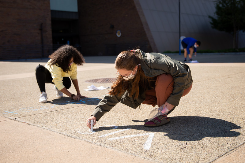 Students use chalk to write messages about voter registration and voting dates on the sidewalk along the Spine near Knox Hall in September 2020. The chalking was organized by the Student Engagement within the Office of Student Life.<br /> <br /> Photographer: Meredith Forrest Kulwicki<br /> <br /> This image has been approved by UB's Office of Environment, Health and Safety to align with current (fall 2020) health and safety regulations during the COVID-19 pandemic.