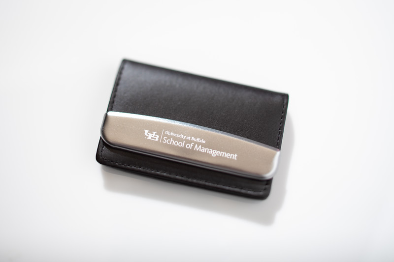 The UB School of Management brand lockup photographed on a business card case in a studio setting in October 2020.<br /> <br /> Photographer: Douglas Levere