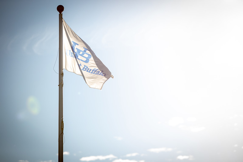 A UB flag new the Student Union with a blue sky on North Campus in Novemebr 2020. <br /> <br /> Photographer: Meredith Forrest Kulwicki<br /> <br /> This image was flipped for the text to read correctly.