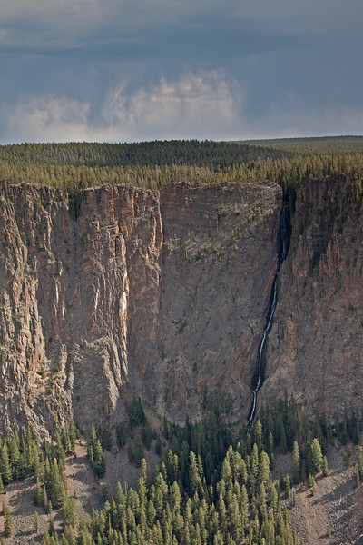 A thunderstorm threatens above the 1200 foot Silver Cord Waterfall flowing into the Yellowstone River Canyon.