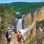 Family taking photos of beautiful waterfall with phone. People on hiking trip in the mountains. Beautiful Lower Falls at Yellowstone National Park, U.S.A.