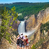 Family relaxing and enjoying beautiful view of waterfall on hiking trip in the mountains. Father with arms around his family. Beautiful Lower Falls at Yellowstone National Park, U.S.A.