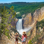 Teenager girls on summer vacation, looking at beautiful waterfall. Beautiful Lower Falls at Yellowstone National Park, U.S.A.