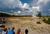 Old Faithful geyser surrounded by excited tourists.