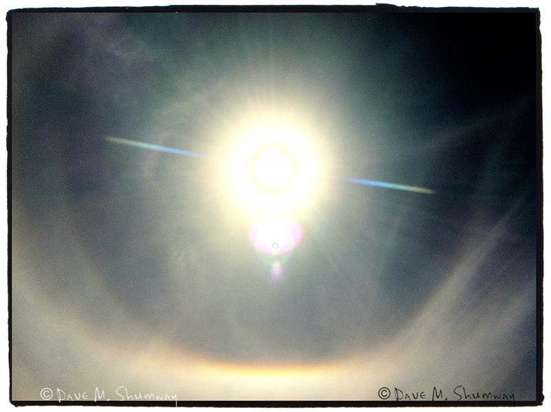 A halo encompasses the sun thanks to a nearby fire.  <br /> iPhone Snap
