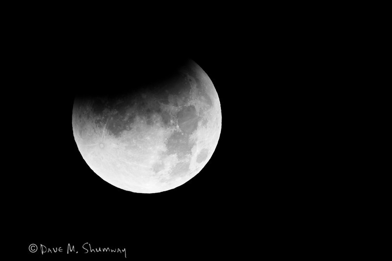 The shadow of Earth slowly creeps across the moon during a total lunar eclipse. Captured with a Canon 7D and 500/4.0L IS + 1.4TC III in aperture priority mode with an exposure bias of - 2/3 at ISO200, f/9.0, and 1/100th of a second. The camera was mounted on a Gitzo 3540XLS tripod and Induro GBH2 head with a custom long lens support. A cable release and LiveView, as mirror lock up, was used.