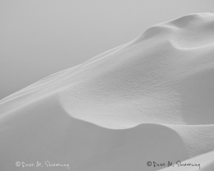 Light plays across drifting snow above the Blacktail Lakes in Yellowstone National Park. Captured with a Canon 5D II and 70-200/2.8L IS II in aperture priority mode with an exposure bias of - 1/3 at ISO200, f/11, and 1/1000th of a second. The camera was handheld.