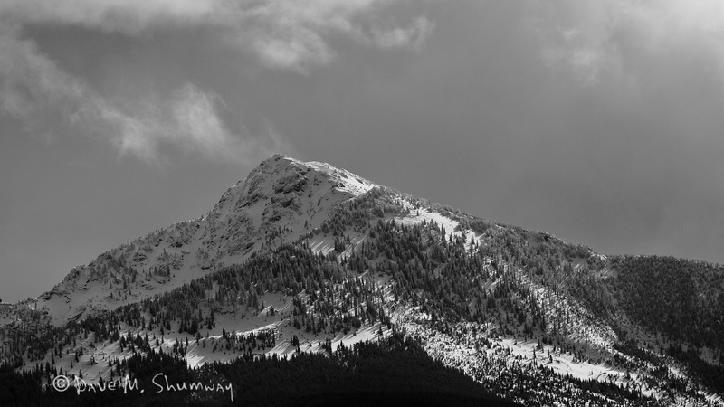 Light plays across mountains to the North of Yellowstone National Park as the wind kicks off snow from the summit. Captured with a Canon 7D and 70-200/2.8L IS II in aperture priority mode with an exposure bias of - 2/3 at ISO200, f/7.1, and 1/2500th of a second. The camera was resting on a beanbag.