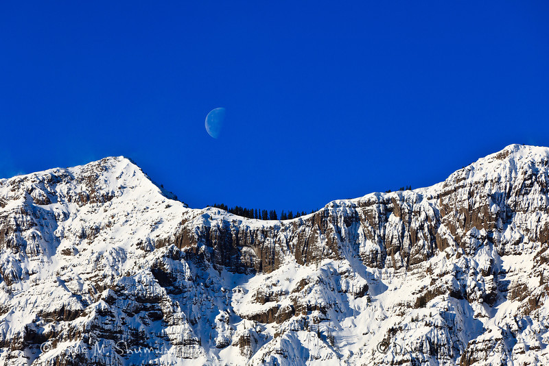 The half moon sets over Barronette Peak el. 10354 feet (3156 m) on a clear morning in Yellowstone National Park. Captured with a Canon 5D II and 70-200/2.8L IS II in aperture priority mode with an exposure bias of 0 at ISO200, f/7.1, and 1/1000th of a second. The camera was handheld.