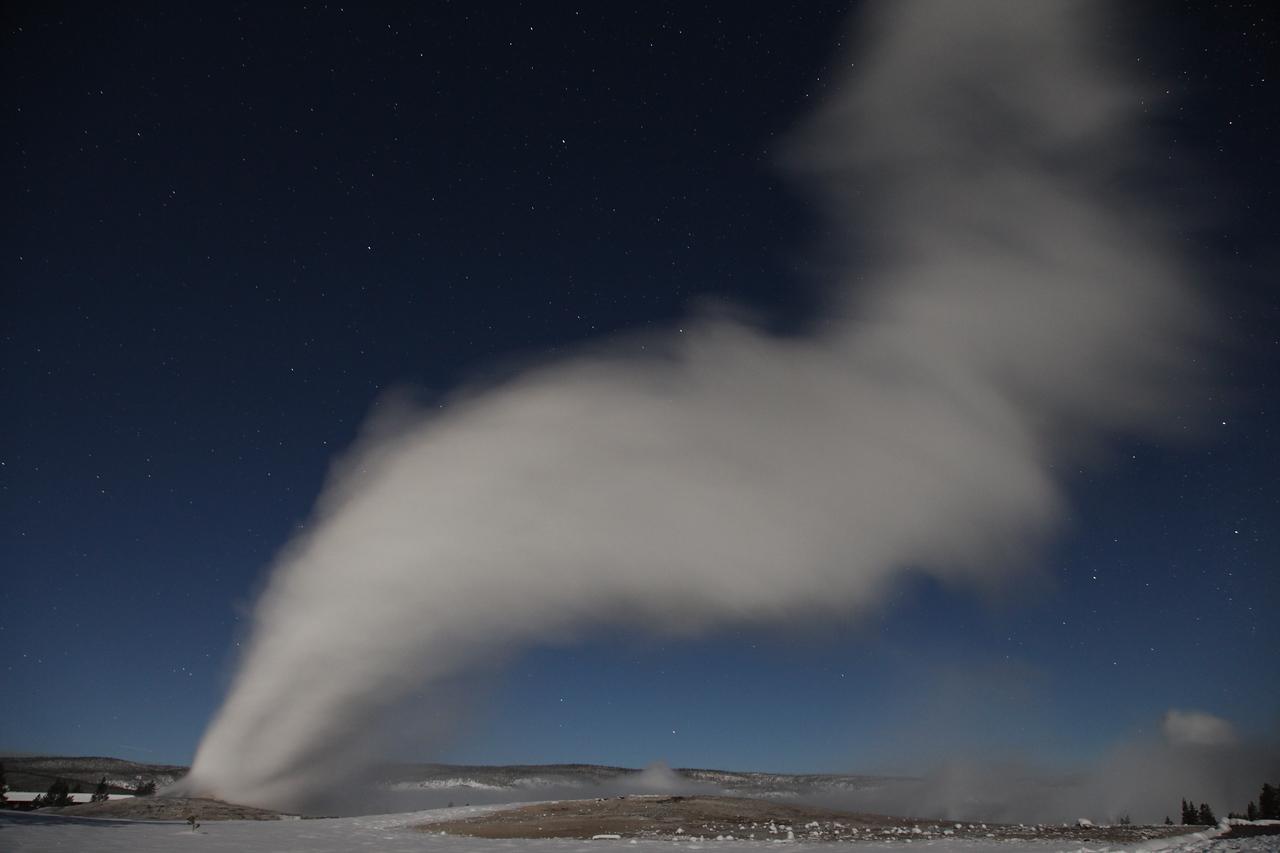 Old faithful eruption at night