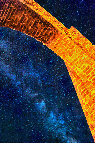 """ All Aglow ""____ 0557Lv<br /> <br /> The Milky Way framed under the Roosevelt Arch<br /> <br /> This unique image is fused directly onto a specially treated, rigid piece of Aluminum.<br /> More archival and lighter than a framed paper print, it arrives ready to hang.<br /> The Float-Mounted MetalPrint™ needs no frame and<br /> will appear to float 3/4"" from your wall.<br /> <br /> Archival paper prints are also available<br /> ------- Contact us for more information -------<br /> moreinfo@RobertHowellPhotography.com"