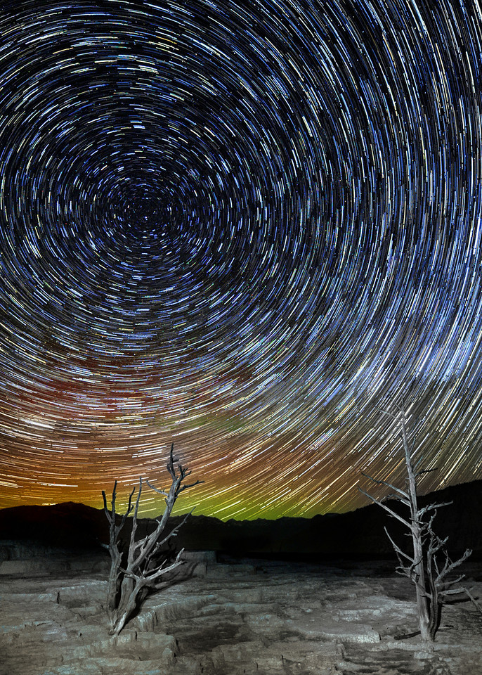 "' A Starry Night '    ____ a Yellowstone Vortex     ____ 453471L<br /> <br /> Colorful Stars Circle all night long<br /> over a Thermal Landscape of Yellowstone<br /> and the Aurora Borealis makes a brief, rare appearance!<br /> <br /> Hang this gorgeous metal print on your wall for a real conversation piece<br /> of your trip to Yellowstone ! <br /> <br /> This unique image is fused directly onto a specially treated, rigid piece of Aluminum.<br /> More archival and lighter than a framed paper print, it arrives ready to hang.<br /> The Float-Mounted MetalPrint™ needs no frame and<br /> will appear to float 3/4"" from your wall.<br /> <br /> Archival paper prints are also available<br /> ------- Contact us for more information -------<br /> moreinfo@RobertHowellPhotography.com"