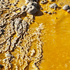 Looks like a toxic ocean, but it's a closeup of the runoff from geysers. The colors are either mineral deposits, bacterial colonies, or both
