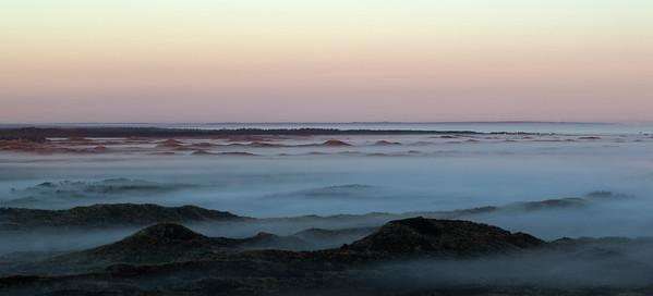 Tågen ligger tungt over klitheden ved solopgang