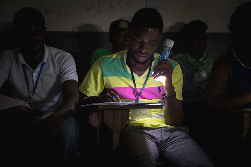 Monrovia, Liberia October 10, 2017 - Poll workers turn on battery operated lights during the vote counting process at a polling station.
