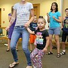 "Brett Outchcunis, better know as ""Ooch"", brought his Ooch World to the Leominster Public Library on Thursday afternoon. He entertained them with some yo-yo tricks and then some group dancing for everyone, even the parents. Dancing together as they enjhoy the show is Leishla Amill and her daughter Leishmari Amill, 4, both of Leominster. SENTINEL & ENTERPRISE/JOHN LOVE"