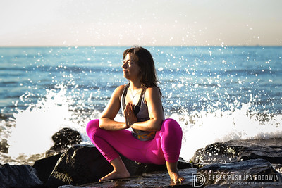 April Dechagas in Malasana (goddess pose) as the waves smash into the rocks on  a peer at Rockaway Beach