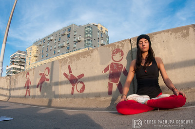 Jivamukti Yoga teacher Meghan Meyer in padmasana with graffiti man tumbling towards her
