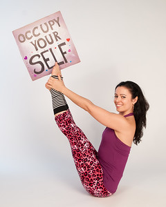 "Sandhi Ferreira in Navasana (boat pose) with ""Occupy Yourself"" sign"