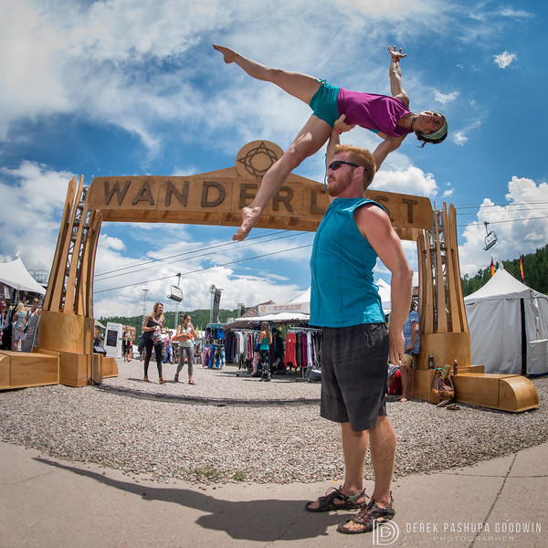 Cheyne Mott holds Michelle Griffith above his head by the Wanderlust sign
