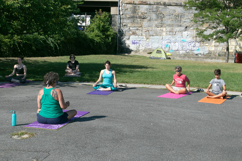Fitchburg yoga instructor Cera Hawkins, back to camera, holds a class at Riverfront Park in the city on Friday mornings at 9:30. SENTINEL & ENTERPRISE/JOHN LOVE