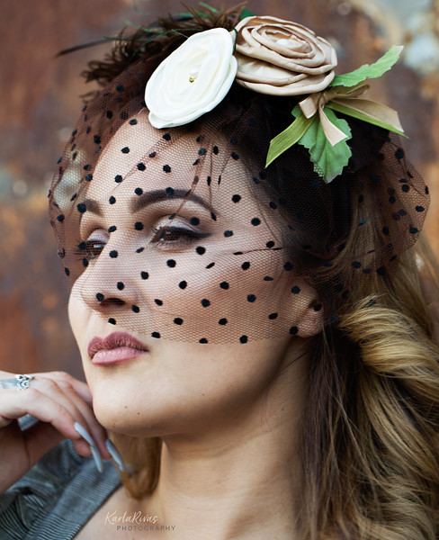 Model Reynalda Fuentes is modeling a Women's flower and fascinator veil design hat made by Chicana artist Yolanda DeLeon McGoogan.