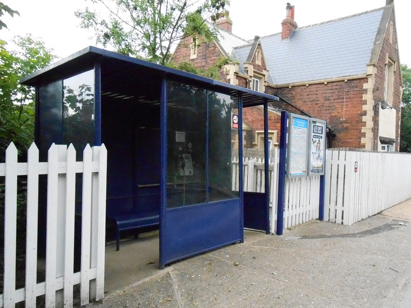 Picture by Liz <br /> <br /> The usual waiting shelter but this one has the bonus of a Telephone <br /> <br /> which is prob like Stanlow & Thornton one of the least used phones <br /> <br /> in the country. I say that because it doesnt take cash it one of the old <br /> <br /> style BT Card phones and from what i read there was no button to <br /> <br /> press for info about train services either!!!