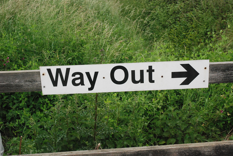 the way out sign on the fence