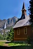 Yosemite Chapel with Upper Yosemite Falls in the background.