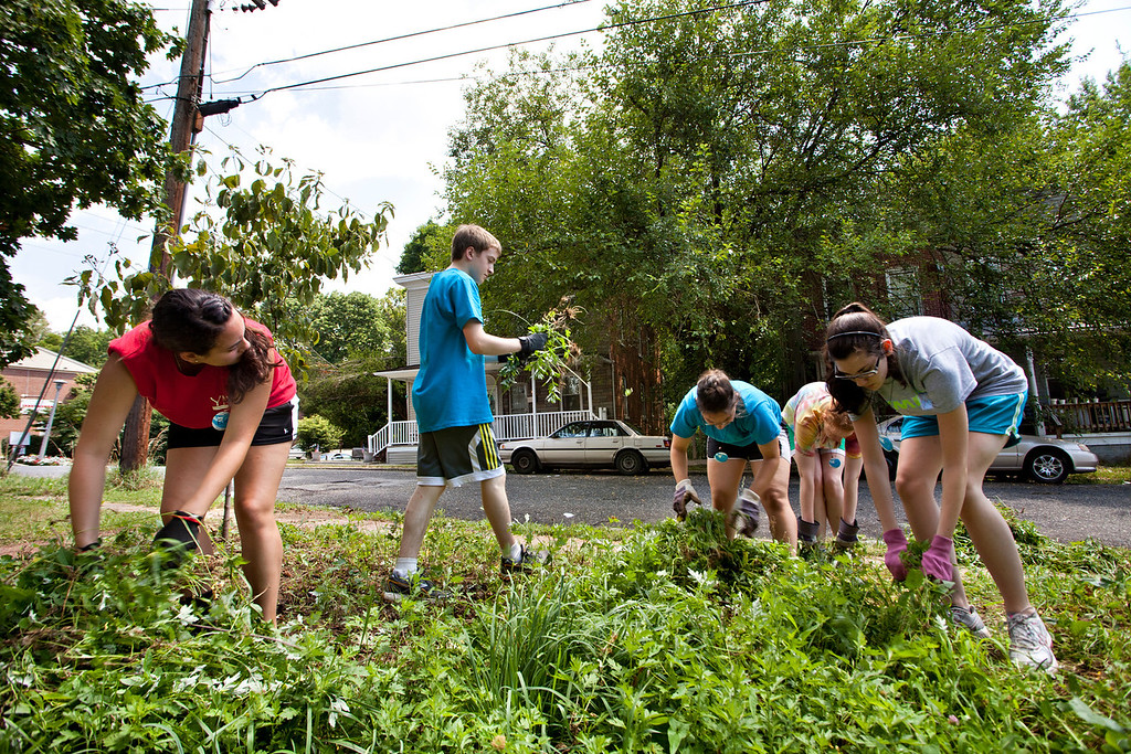 Volunteers from St. Pius V in Lynn, Mass. clean up the Peace Park in Irvington July 10 where they volunteered as part of the Young Neighbors in Solidarity program.