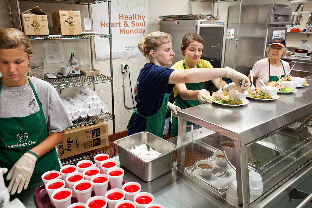 Kayla DiBiasie, Gillian Krans and Bridget Shreve work behind the food counter at The Franciscan Center July 10 where they volunteered with others as part of the Young Neighbors in Solidarity program.
