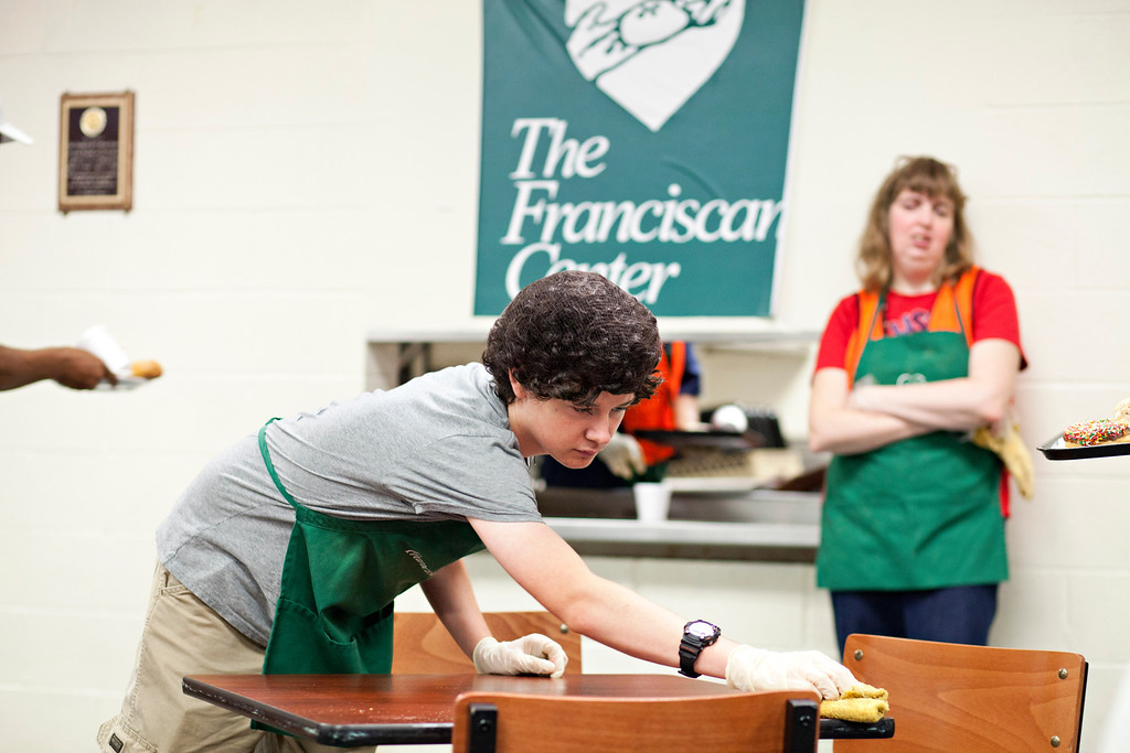 Michael O'Connor wipes off a table at The Franciscan Center July 10 where he volunteered with others as part of the Young Neighbors in Solidarity program.