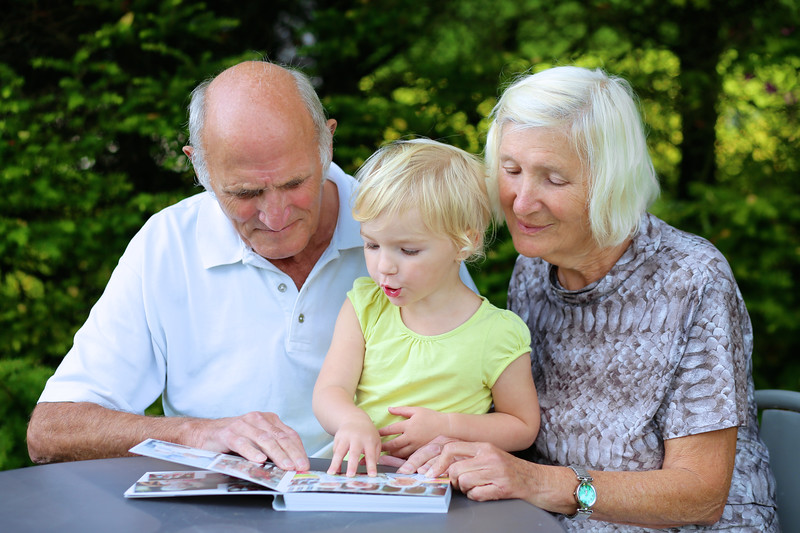 Grandparents with grandchild watching photos in album