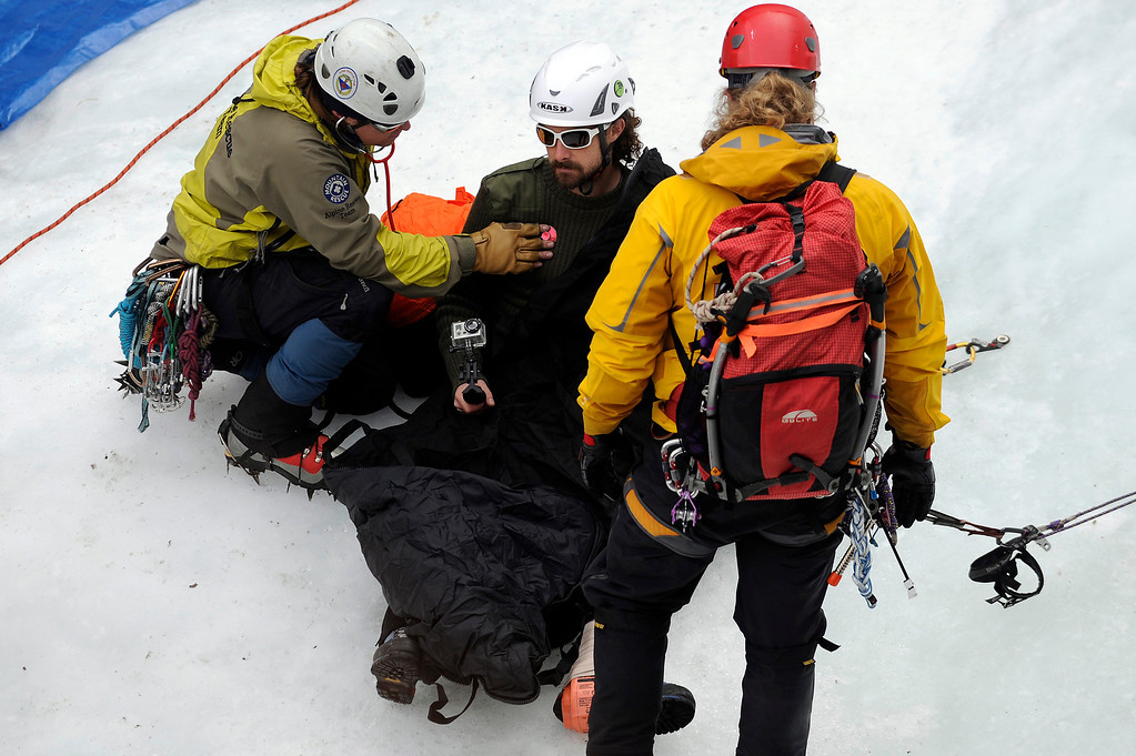 . GOLDEN, CO - FEBRUARY 16:  Zach Taylor, left, checks Charlie Adams vital signs during an ice climbing rescue training by the Alpine Rescue Team in Clear Creek Canyon near Golden, Colorado on February 16, 2014. The Alpine Rescue Team is one of a handful of nationally accredited mountain rescue team in Colorado. They specialize in rescue services in hard-to-reach areas and conditions. (Photo by Seth McConnell/The Denver Post)