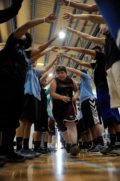. WESTMINSTER, CO - APRIL 8: Nelly Grantham (13) of Horizon High School runs through a tunnel of students as she is introduced before a unified basketball game at Mountain Range High School in Westminster, Colorado on April 8, 2014. The Adams 12 Five Star Schools Athletic Department and Student Support Services have been working in collaboration with Special Olympics to develop a unified sports program in the district. Each of the district�s five comprehensive high schools has its own basketball team that consists of students with and without disabilities. (Photo by Seth McConnell/The Denver Post)