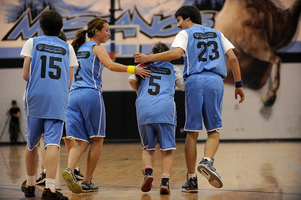 . WESTMINSTER, CO - APRIL 8: Sasha Hernandez (5) of Mountain Range High School is congratulated by teammates Maggie Castillo (2) and Travis Younger (23) after making a basket during a unified basketball game at Mountain Range High School in Westminster, Colorado on April 8, 2014. The Adams 12 Five Star Schools Athletic Department and Student Support Services have been working in collaboration with Special Olympics to develop a unified sports program in the district. Each of the district�s five comprehensive high schools has its own basketball team that consists of students with and without disabilities. (Photo by Seth McConnell/The Denver Post)