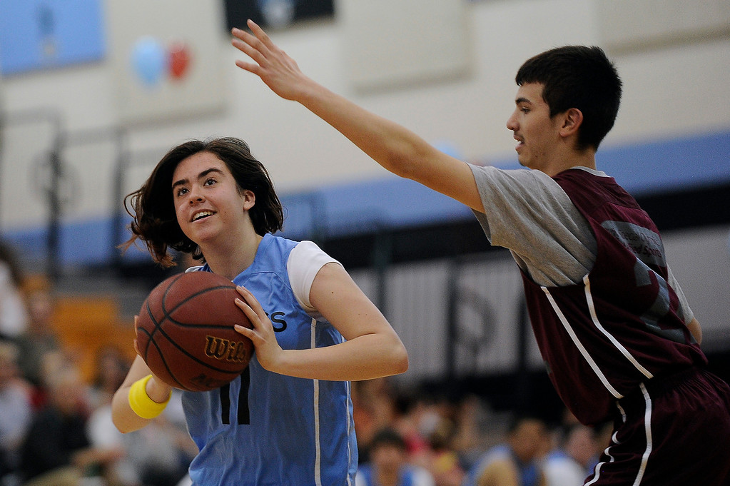 . WESTMINSTER, CO - APRIL 8: Morgan Shelton (11) of Mountain Range High School looks to take a shot as she is pressured by Alex Rivera (22) of Horizon High School during a unified basketball game at Mountain Range High School in Westminster, Colorado on April 8, 2014. The Adams 12 Five Star Schools Athletic Department and Student Support Services have been working in collaboration with Special Olympics to develop a unified sports program in the district. Each of the district�s five comprehensive high schools has its own basketball team that consists of students with and without disabilities. (Photo by Seth McConnell/The Denver Post)