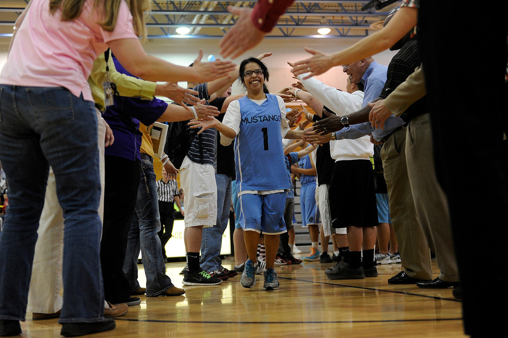 . WESTMINSTER, CO - APRIL 8: Nirvana Maldonado (1) of Mountain Range High School runs through a tunnel of students as she is introduced before a unified basketball game at Mountain Range High School in Westminster, Colorado on April 8, 2014. The Adams 12 Five Star Schools Athletic Department and Student Support Services have been working in collaboration with Special Olympics to develop a unified sports program in the district. Each of the district�s five comprehensive high schools has its own basketball team that consists of students with and without disabilities. (Photo by Seth McConnell/The Denver Post)