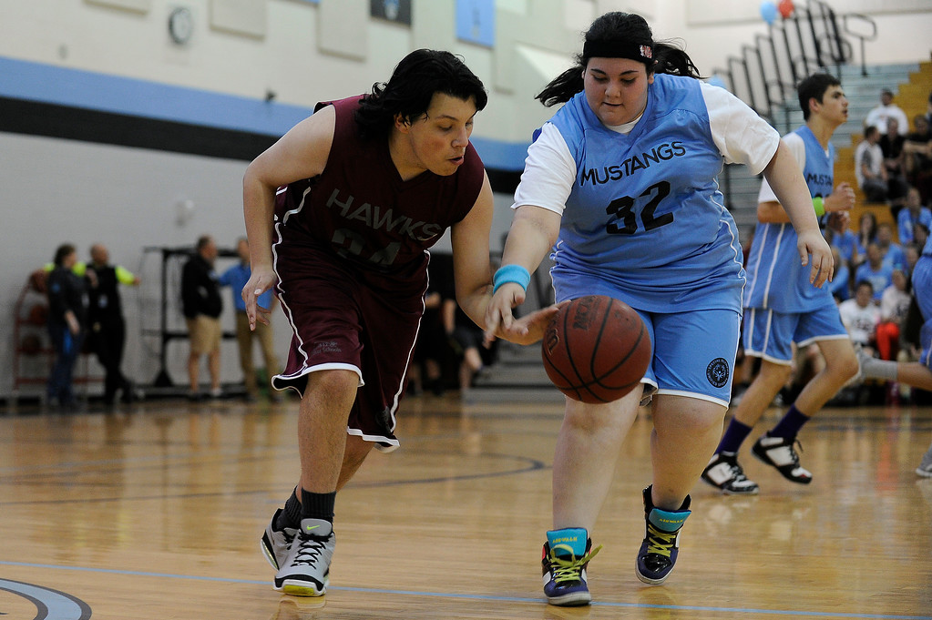 . WESTMINSTER, CO - APRIL 8: Nalicia Straub (32) of Mountain Range High School goes for the steal as Nicholas Aragon of Horizon High School dribbles the ball up court during a unified basketball game at Mountain Range High School in Westminster, Colorado on April 8, 2014. The Adams 12 Five Star Schools Athletic Department and Student Support Services have been working in collaboration with Special Olympics to develop a unified sports program in the district. Each of the district�s five comprehensive high schools has its own basketball team that consists of students with and without disabilities. (Photo by Seth McConnell/The Denver Post)