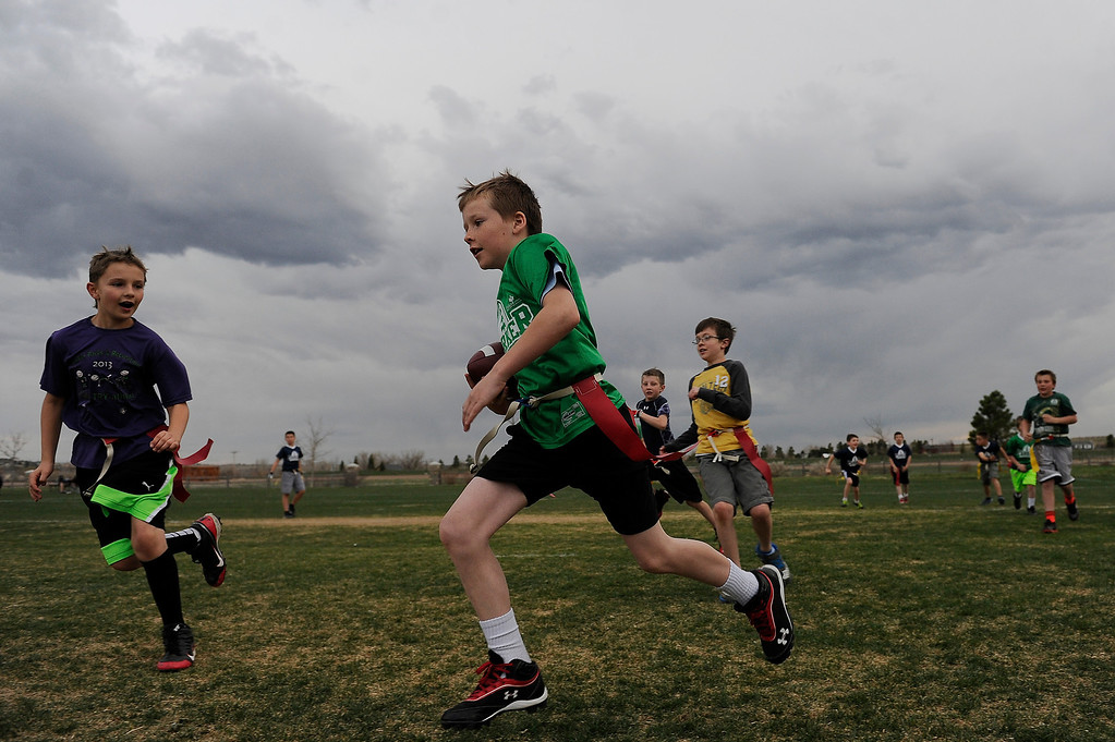 . PARKER, CO - APRIL 18: Johnny Seely sprints past a defender as he runs up field during flag football practice at Salisbury Equestrian Park and Sports Complex in Parker, Colorado on April 18, 2014. Parker recently purchased 90 acres north of the existing Salisbury Equestrian Park and Sports Complex and are looking for feedback for possible uses. (Photo by Seth McConnell/The Denver Post)