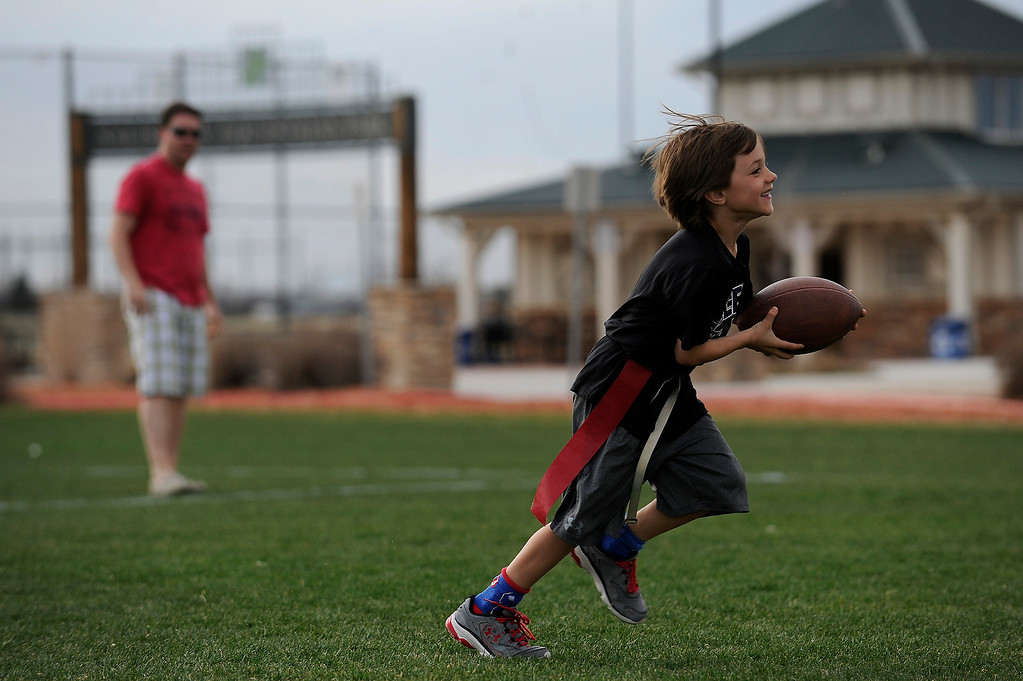 . PARKER, CO - APRIL 18: Harrison Dishong, 7, catches a pass from his dad, Scott Dishong, as he warms up before flag football practice at Salisbury Equestrian Park and Sports Complex in Parker, Colorado on April 18, 2014. Parker recently purchased 90 acres north of the existing Salisbury Equestrian Park and Sports Complex and are looking for feedback for possible uses. (Photo by Seth McConnell/The Denver Post)