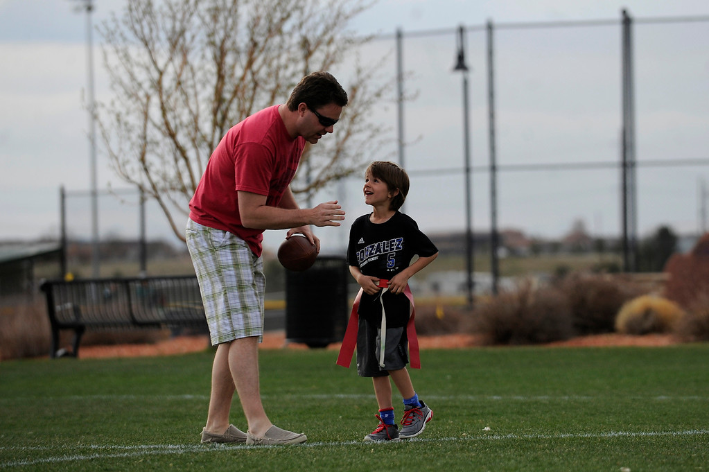 . PARKER, CO - APRIL 18: Scott Dishong tells his son, Harrison Dishong, 7, which route to run as they play catch before flag football practice at Salisbury Equestrian Park and Sports Complex in Parker, Colorado on April 18, 2014. Parker recently purchased 90 acres north of the existing Salisbury Equestrian Park and Sports Complex and are looking for feedback for possible uses. (Photo by Seth McConnell/The Denver Post)