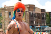 Shirtless man in a colorful wig rides on a float in the Chicago Gay Pride Parade.