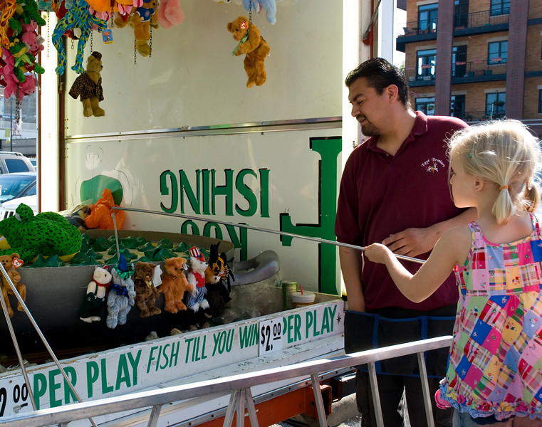 Young girl playing a frog fishing carnival game. May Fest Chicago is produced by a German group known as the Mardi Gras Society in the Lincoln Square neighborhood in Chicago, Illinois. The festival promotes German culture, including food, dance, music, and traditional clothing.