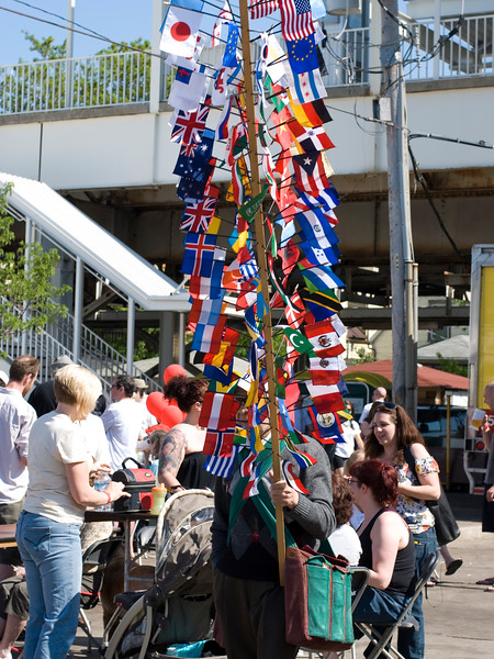 Flags of countries sold by a vendor. May Fest Chicago is produced by a German group known as the Mardi Gras Society in the Lincoln Square neighborhood in Chicago, Illinois. The festival promotes German culture, including food, dance, music, and traditional clothing.