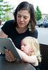 Caucasian mother and daughter interact with Apple iPad together at an outdoor cafe