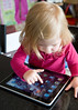Caucasian toddler uses Apple iPad applications to entertain herself and learn